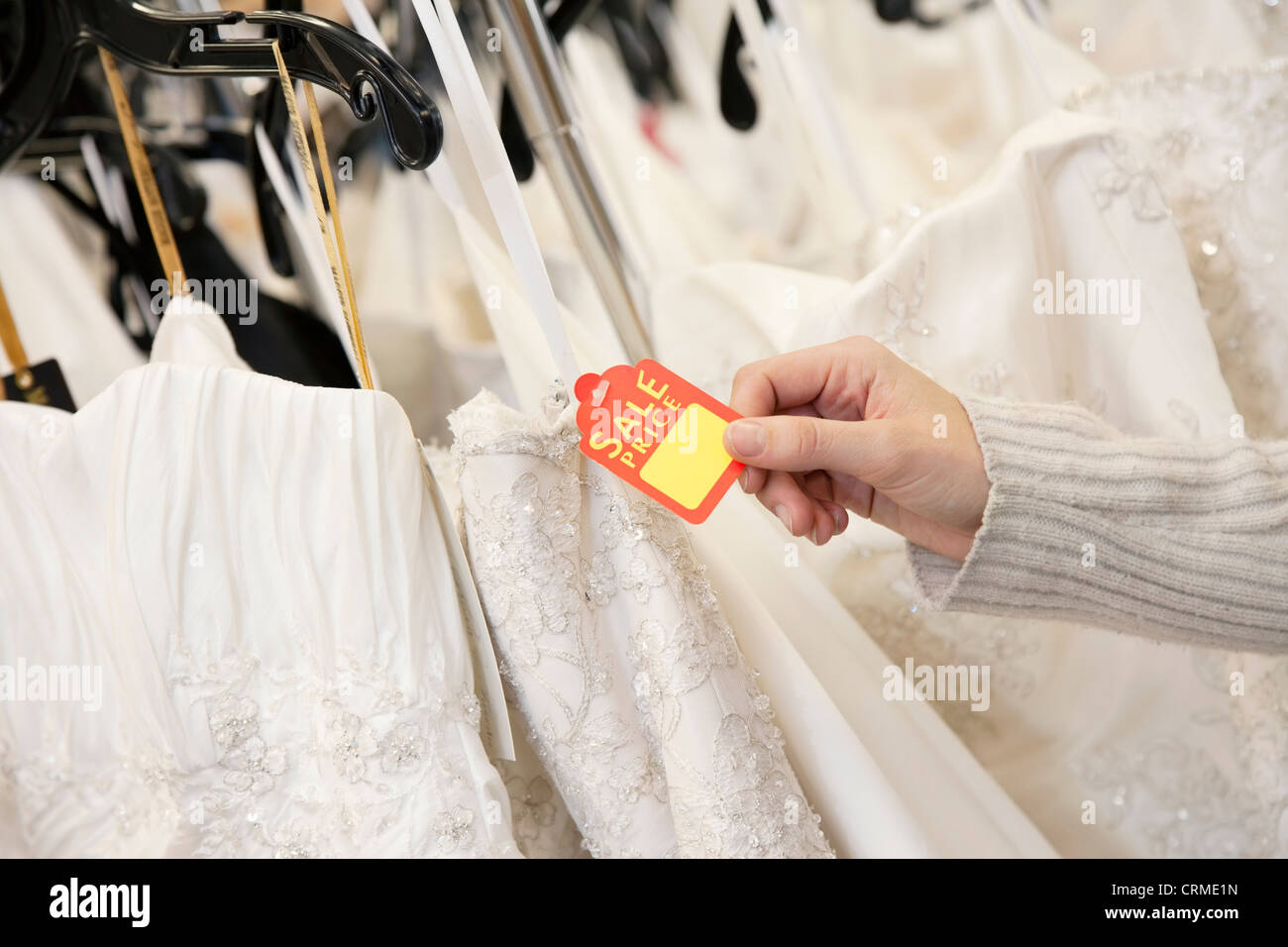 Cropped shot of female hands holding price tag attached to wedding gown in bridal boutique - Stock Image
