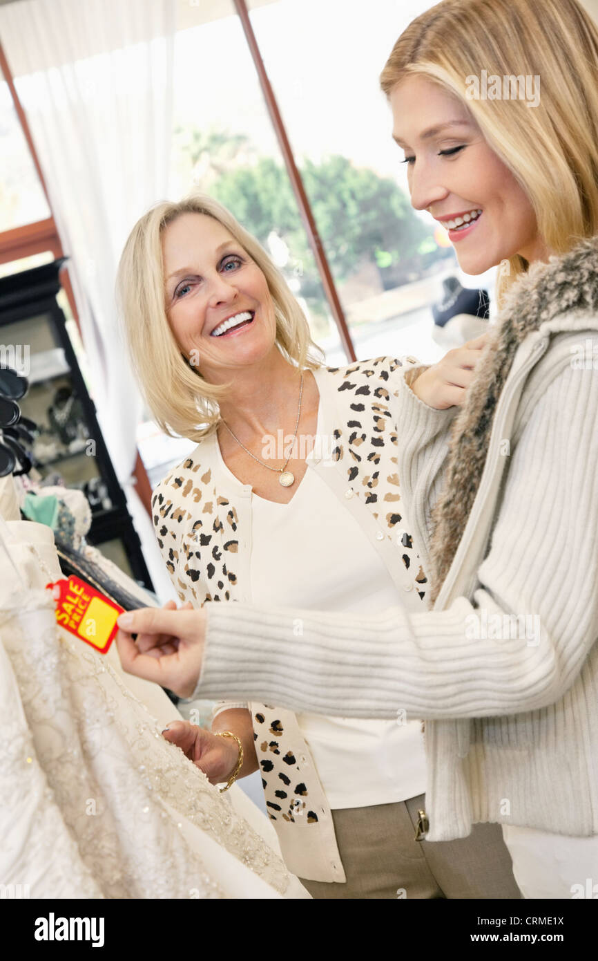 Cheerful mother and daughter looking at price tag of wedding gown in bridal store - Stock Image