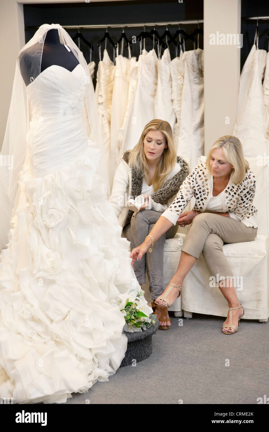 fdc8ea9cd0c Beautiful young woman sitting with mother while looking at wedding gown in  bridal store - Stock