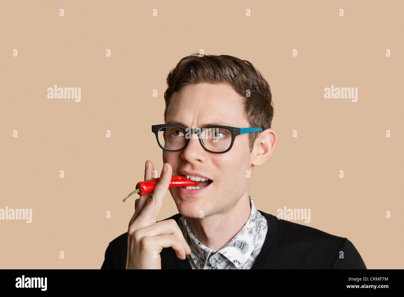 Mid adult man smoking red chili pepper over colored background - Stock Image