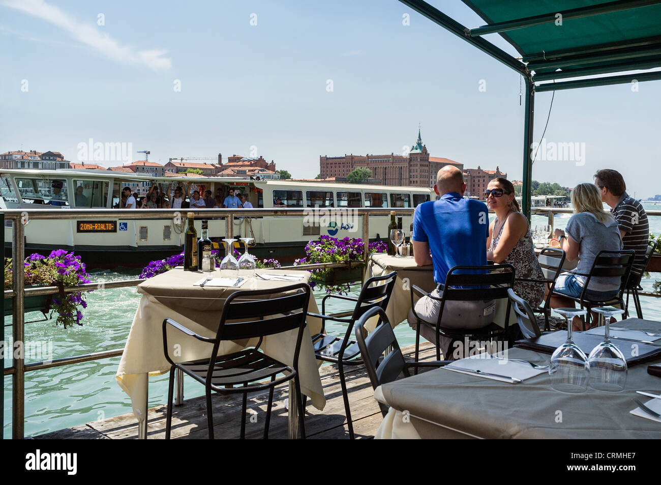 A valporetto passing diners eating out at a canal side restaurant in Dorsoduro Venice. - Stock Image