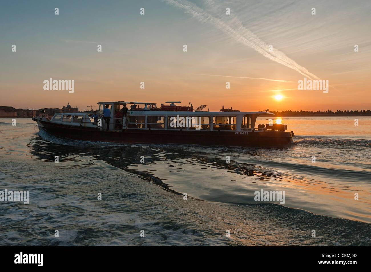 A valporetto or water bus crossing the Venice Lagoon at sunset - Stock Image
