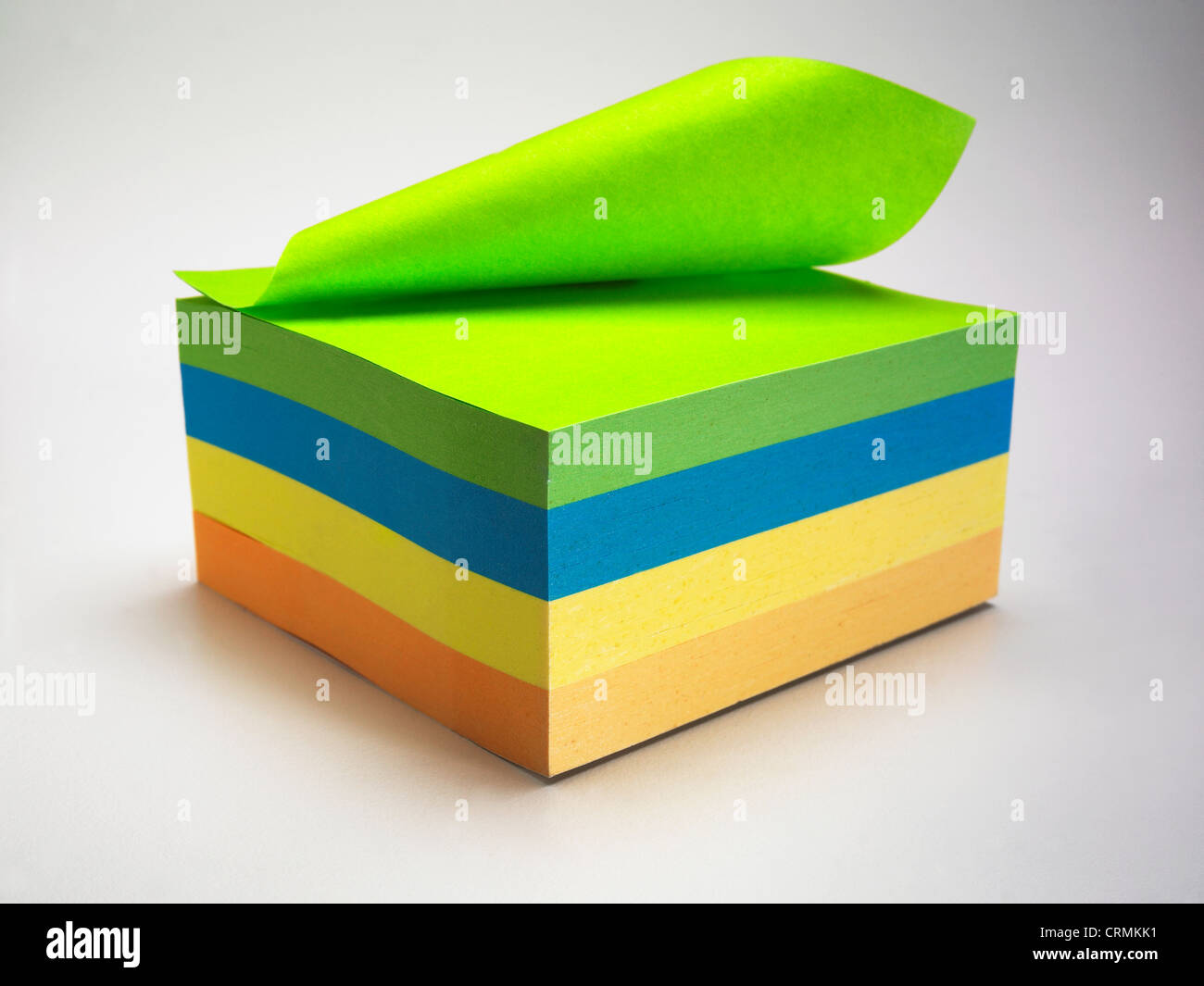 A block of coloured sticky notes, one folded back - Stock Image