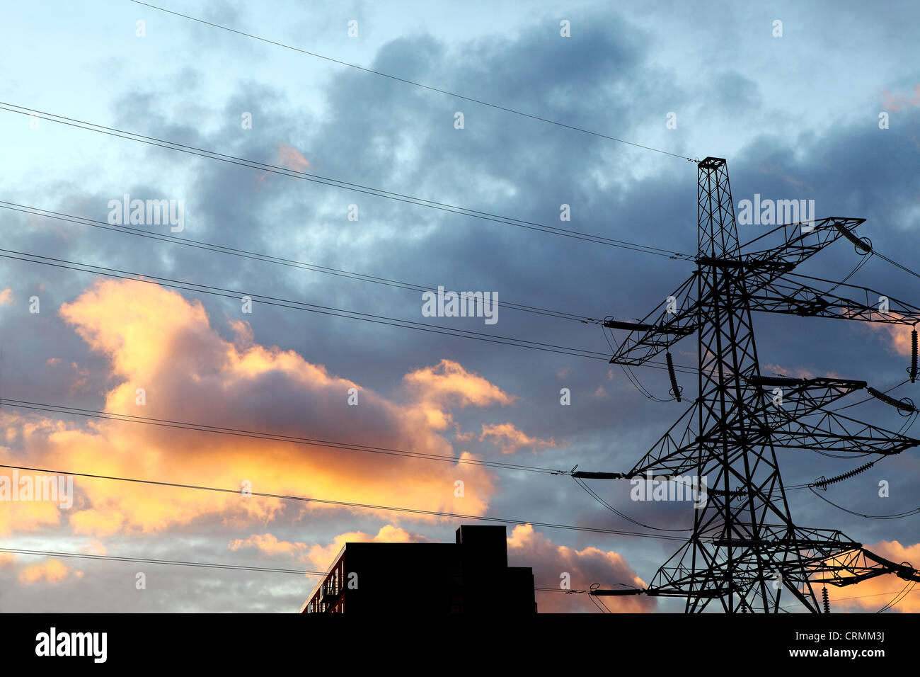 An electricity pylon against a cloudy sky at sunset - Stock Image