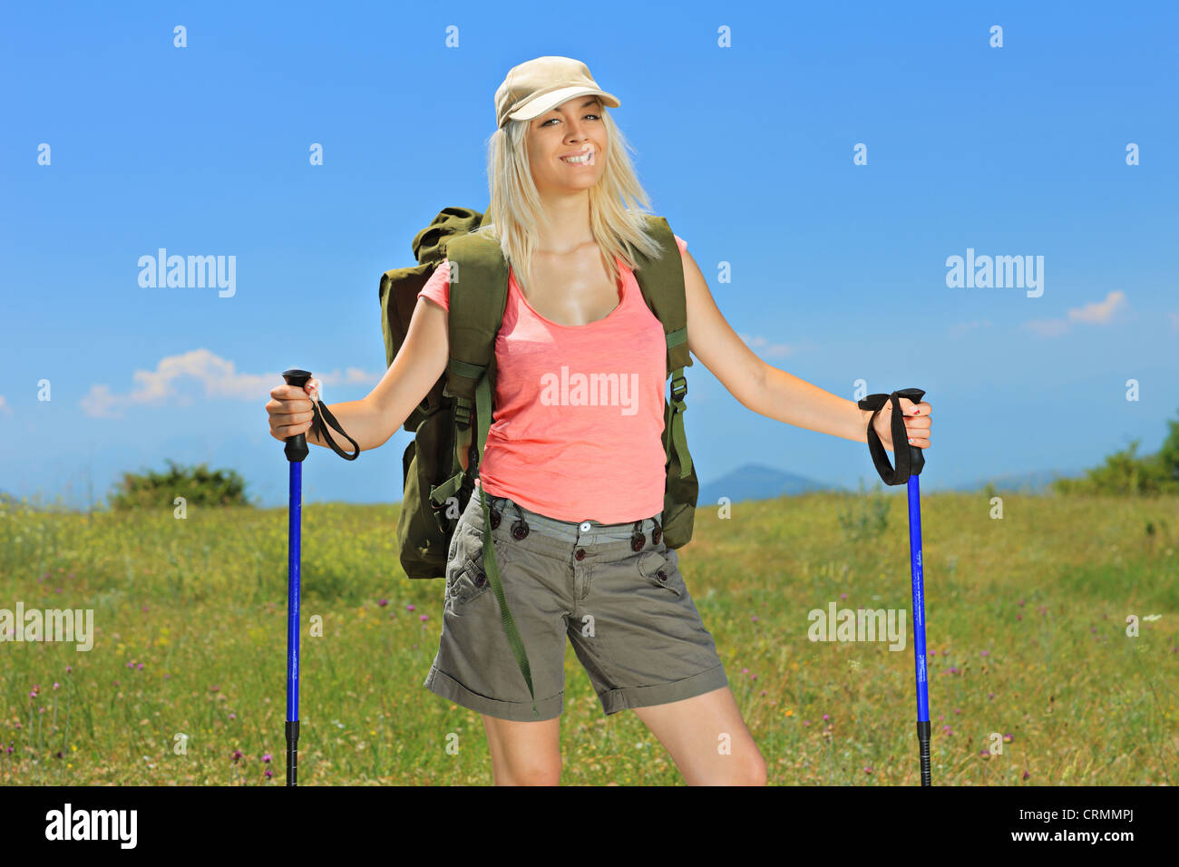A smiling woman posing with backpack and hiking poles posing outdoor - Stock Image