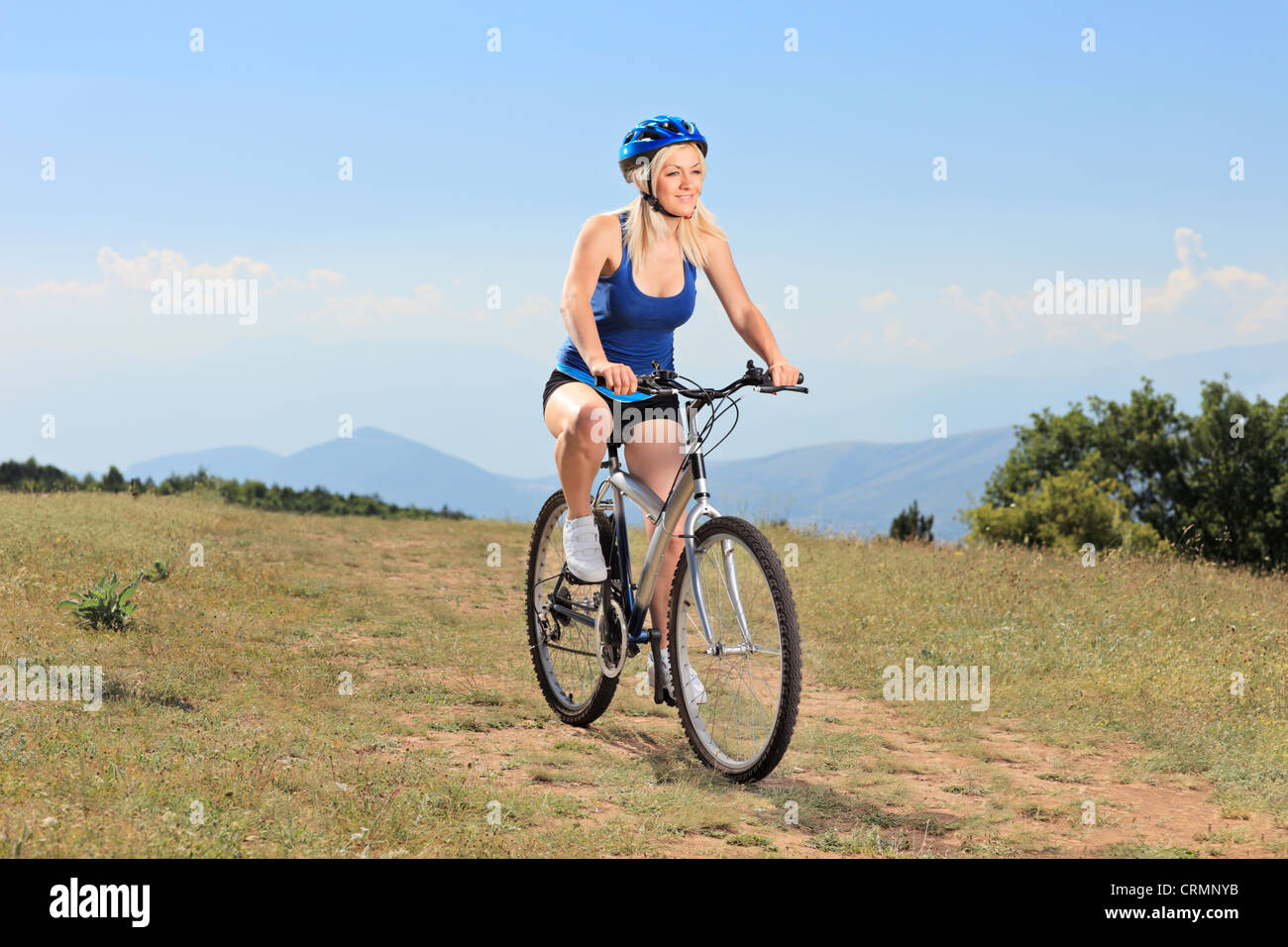 Young female bicyclist riding on a mountain - Stock Image