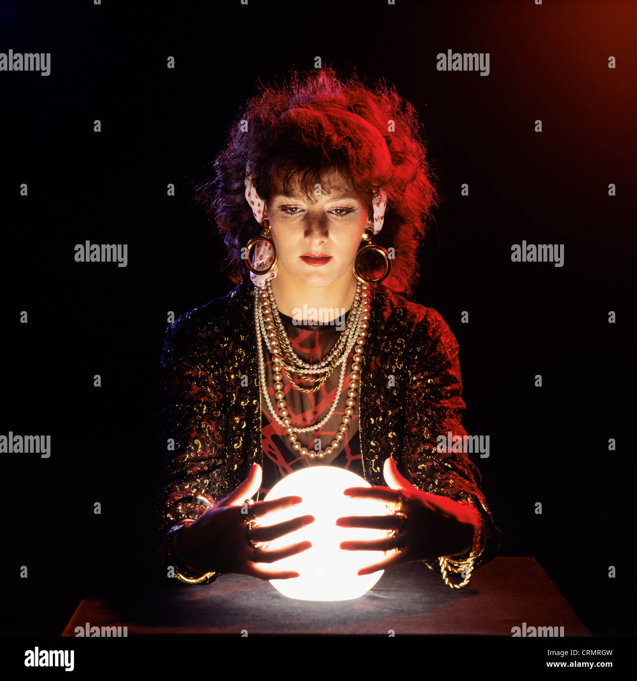 Gipsy fortune teller with lit crystal ball - Stock Image