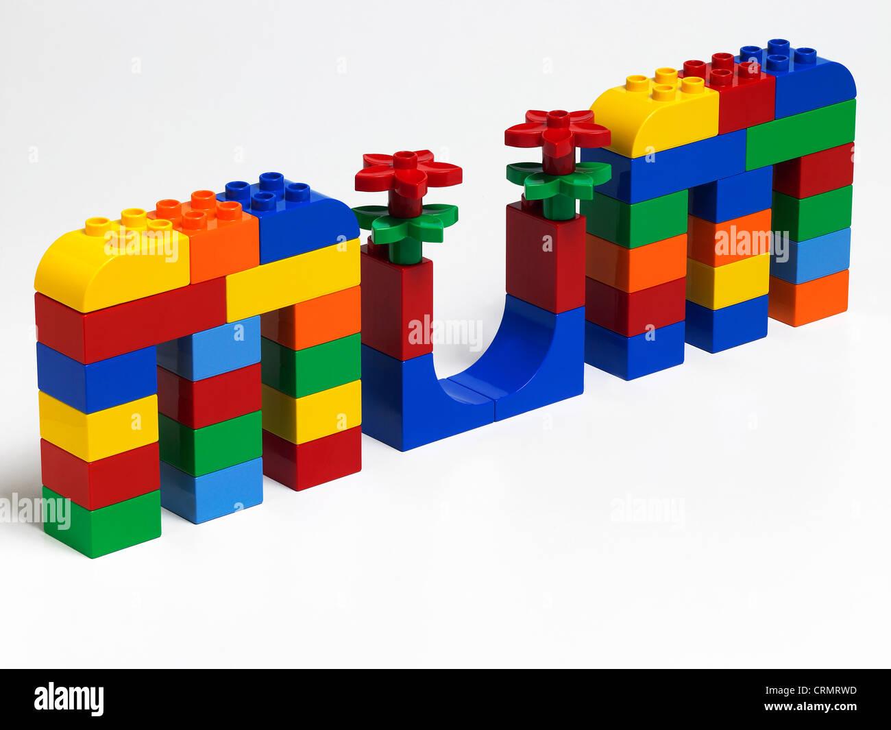 Coloured plastic building bricks spelling the word Mum - Stock Image