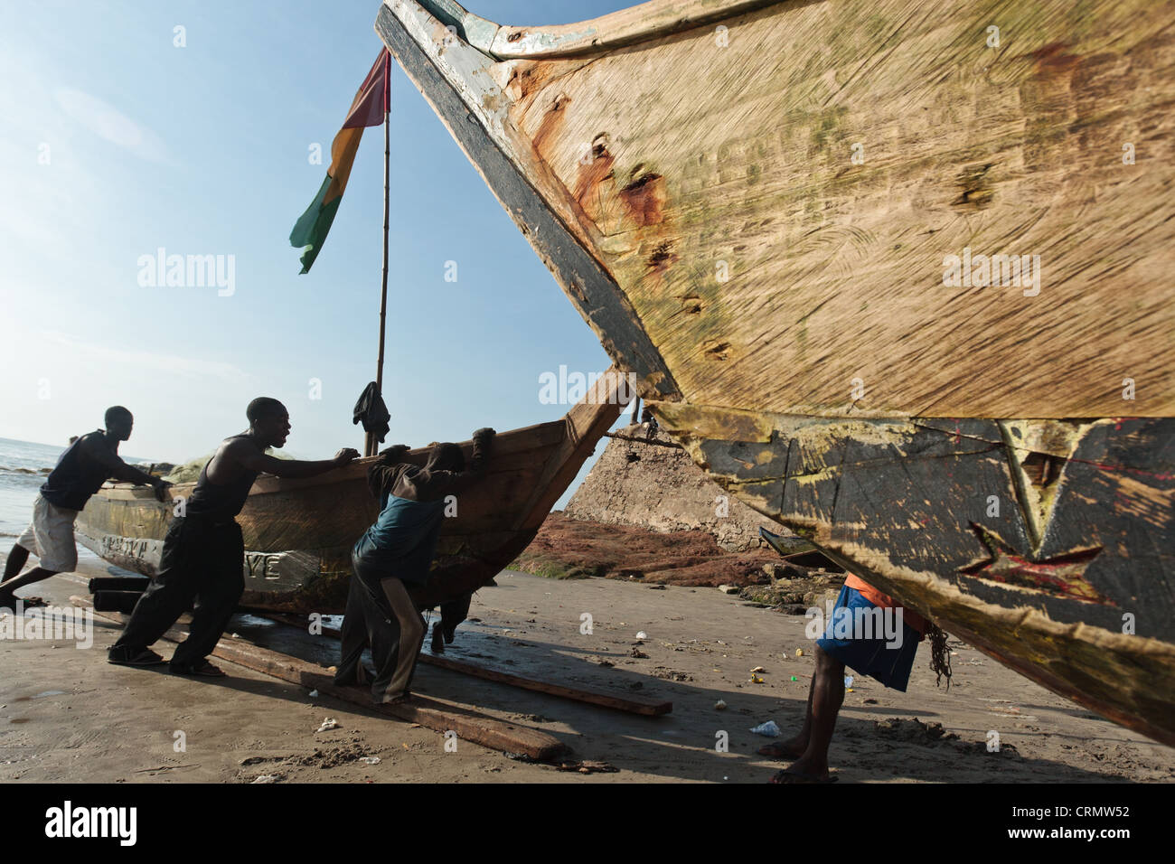 Fishermen pulling their boat on the beach in Cape Coast, Ghana - Stock Image