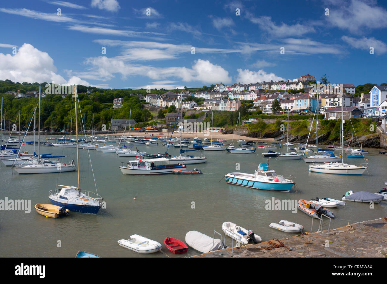 New Quay harbour at high tide with boats and colourful terraced houses on hill behind Ceredigion Mid Wales UK - Stock Image