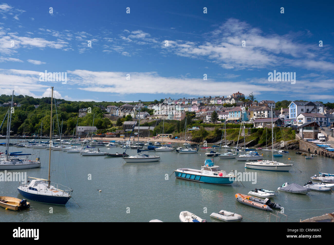 New Quay harbour and beach at high tide with boats and colourful terraced houses on hill behind Ceredigion Mid Wales - Stock Image