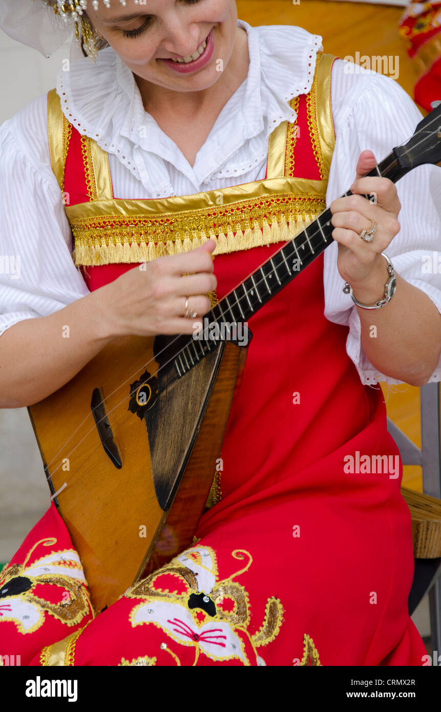 Ukraine, Yalta, Livadia Palace. Ukrainian folkloric show. Woman in traditional costume playing Russian three-stringed - Stock Image