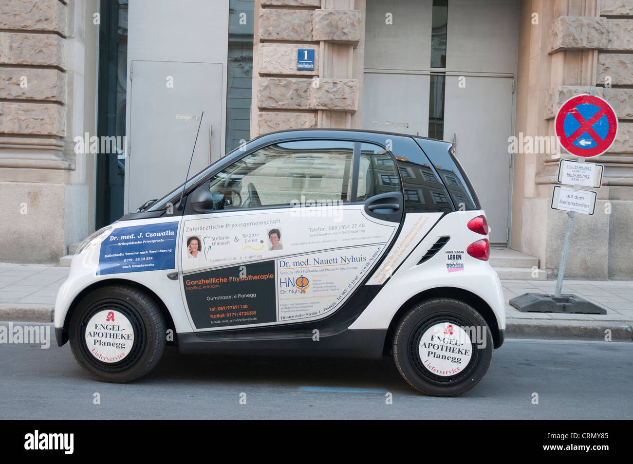 Small car parked in Munich, covered with advertising for doctors and medical products - Stock Image
