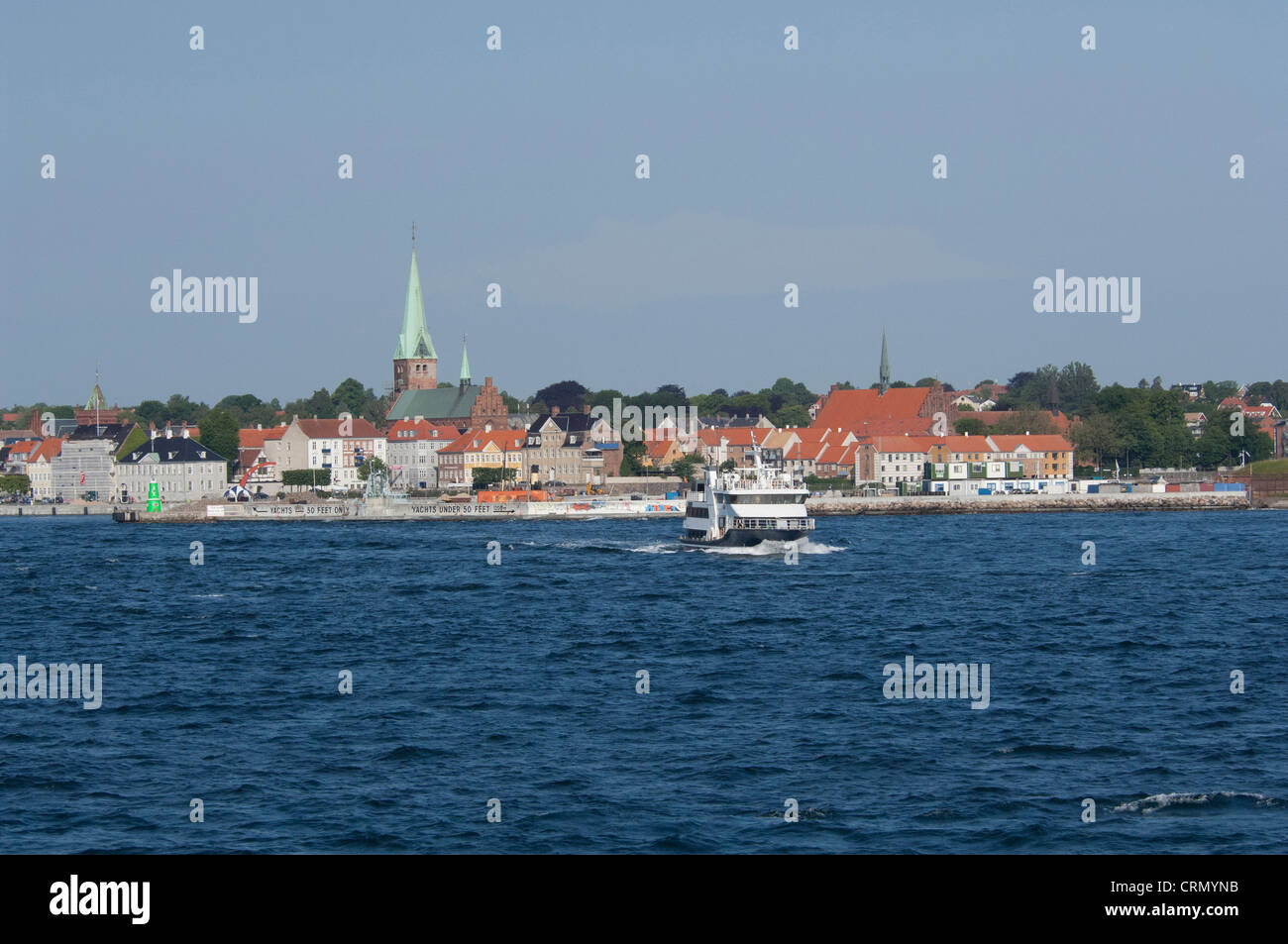 Denmark, Helsingoer. North Sea view of the port area of Helsingoer and historic city skyline with local ferry. - Stock Image