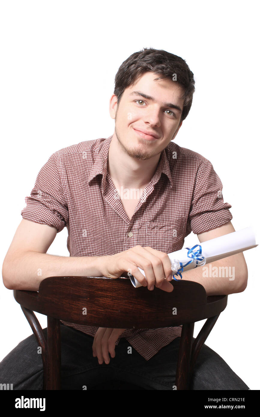 High school male graduate holding his graduating diploma sitting on a chair on a white background - Stock Image