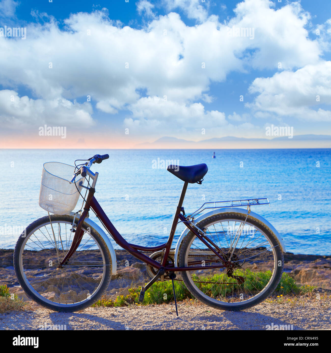 Bicycle in formentera beach on Balearic islands with Ibiza sunset background - Stock Image