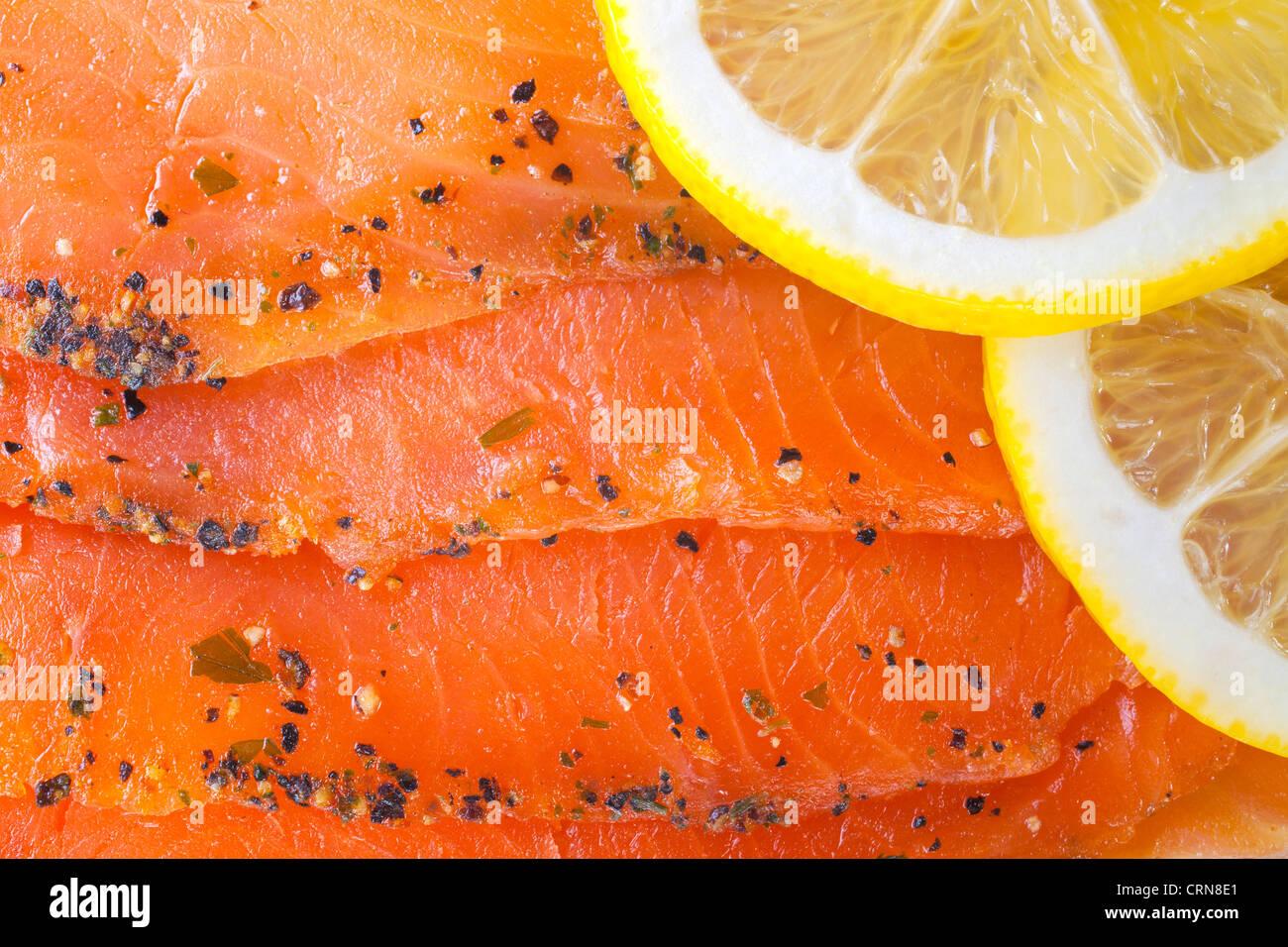 Seasoned smoked salmon with lemon slices - Stock Image