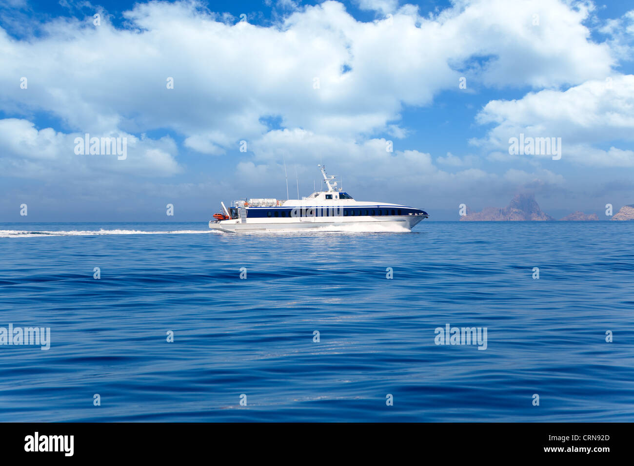 Boat ferry cruising Ibiza to Formentera with Es Vedra in background - Stock Image