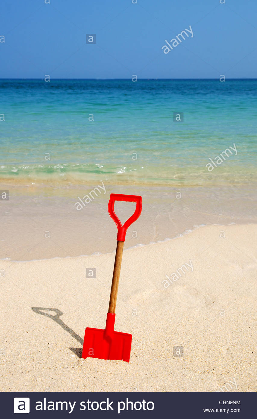 A childs red toy spade in the sand on a beach in cornwall, uk - Stock Image
