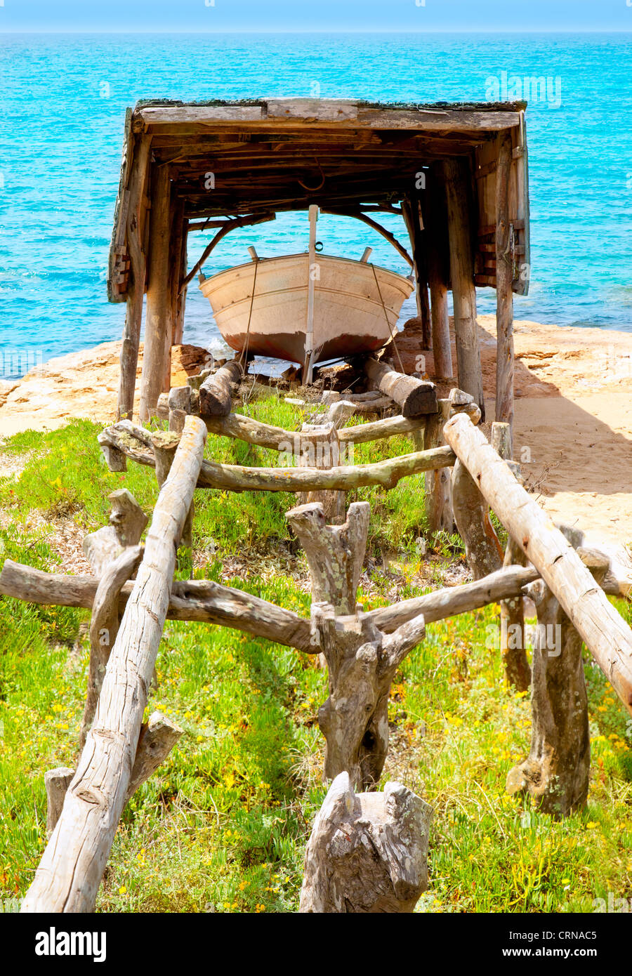beached boat with traditional wood railway in Formentera Balearic islands - Stock Image