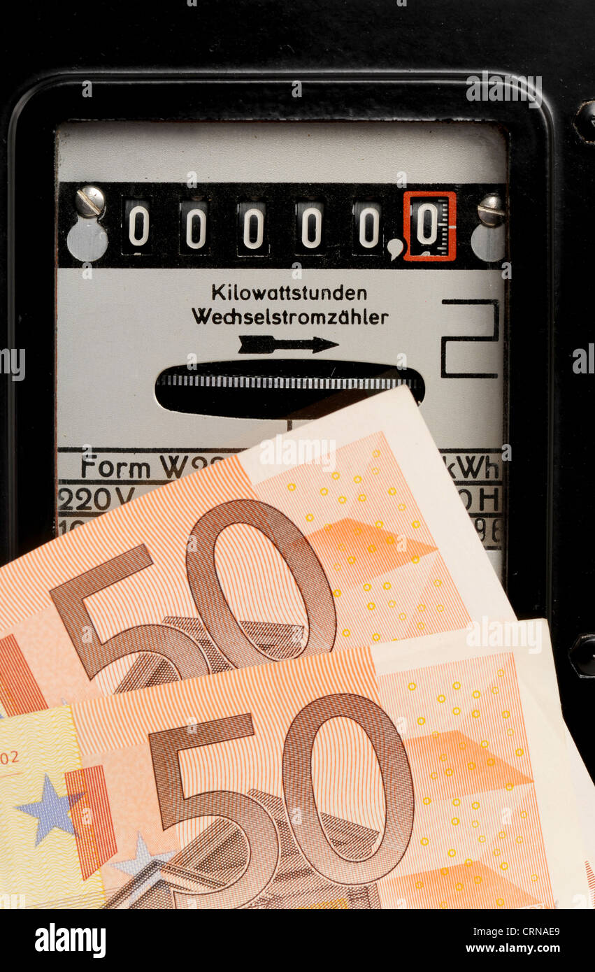 Old electricity meter and Euro-banknotes in front of a white background - Stock Image