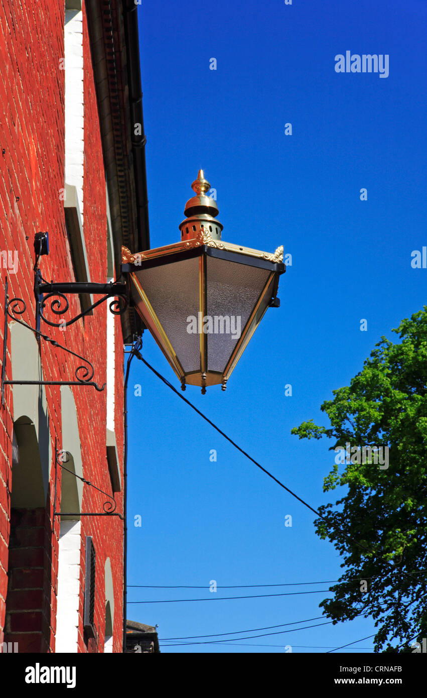 A view of an ornate outside lamp on the front of a Georgian style building at New Buckenham, Norfolk, England, United - Stock Image