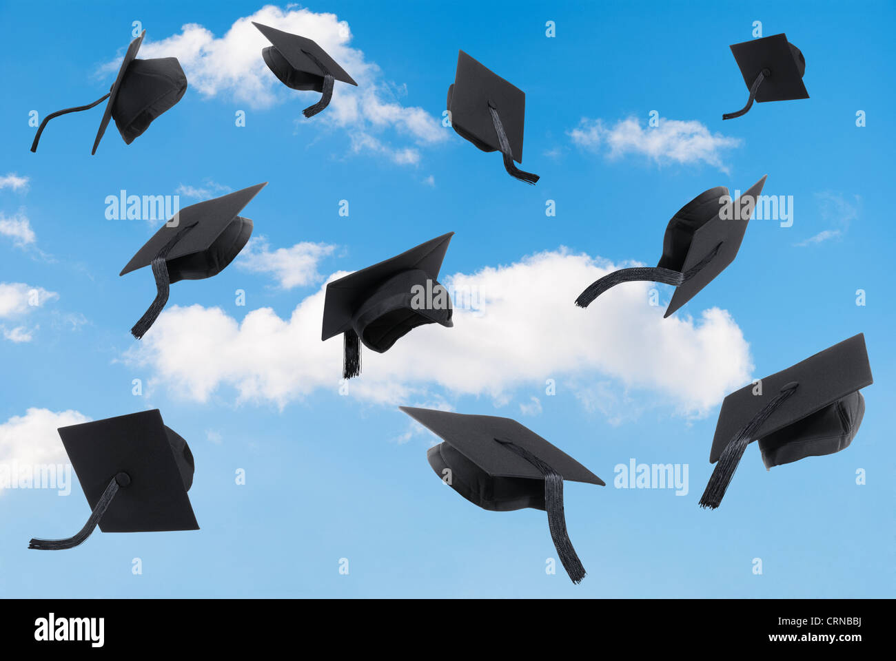Graduation mortar boards thrown into a blue sky - Stock Image