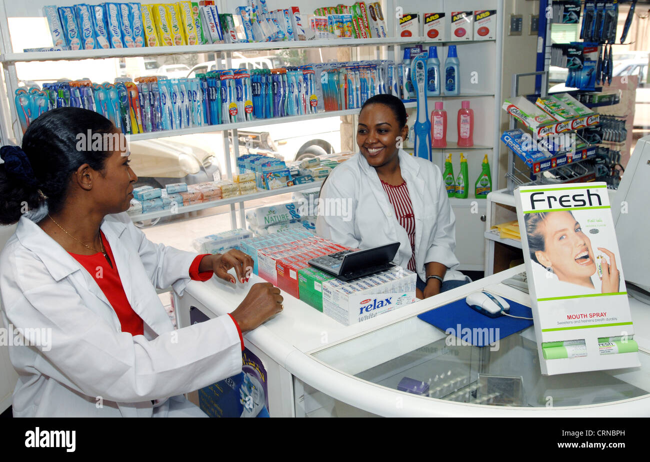 Female Pharmacist And Cashier Discuss Current Medical Supplies Stock