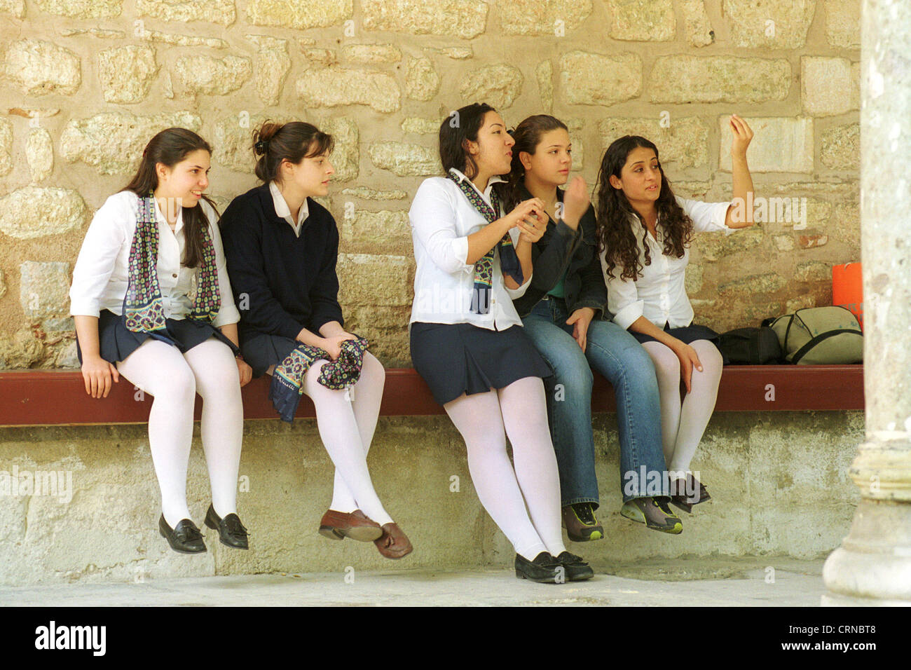Schoolgirls sitting on a bench, Istanbul - Stock Image