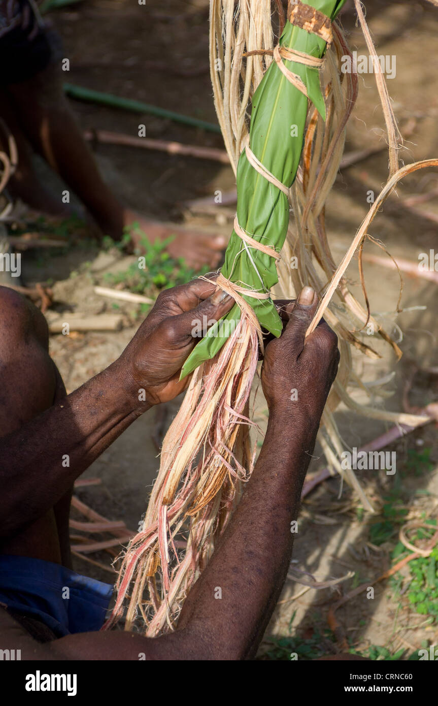 Man tying vines in leaves to keep them supple ready for the Nagol land-diving ceremony, Pentecost Island, Vanuatu - Stock Image