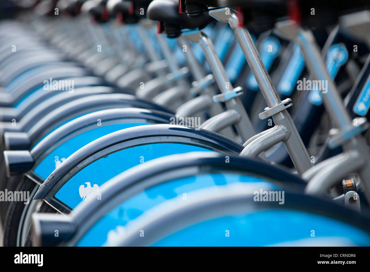A row of Barclays Cycle hire scheme bikes in a docking station. - Stock Image