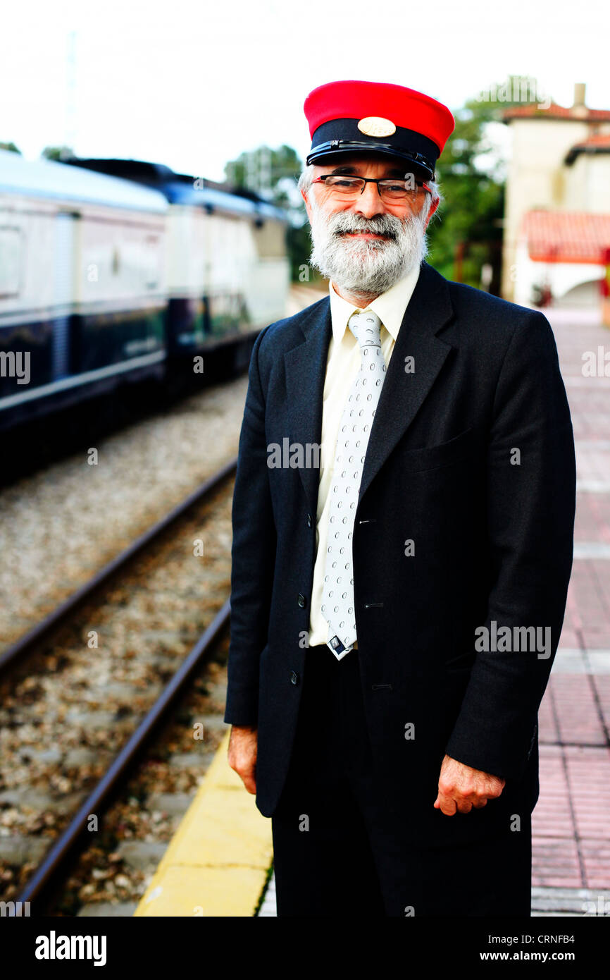 Guard at a FEVE station with the Transcantabrico train on the background, Spain. - Stock Image