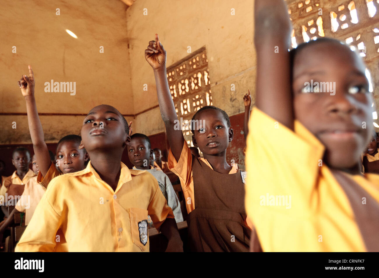 Grade three students raise their hands to answer their teacher's question during a mathematics class at the - Stock Image