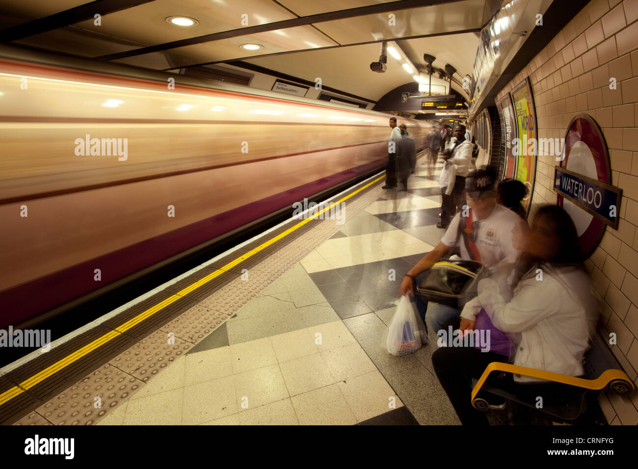 A Northern line tube train passing through Waterloo underground station. - Stock Image