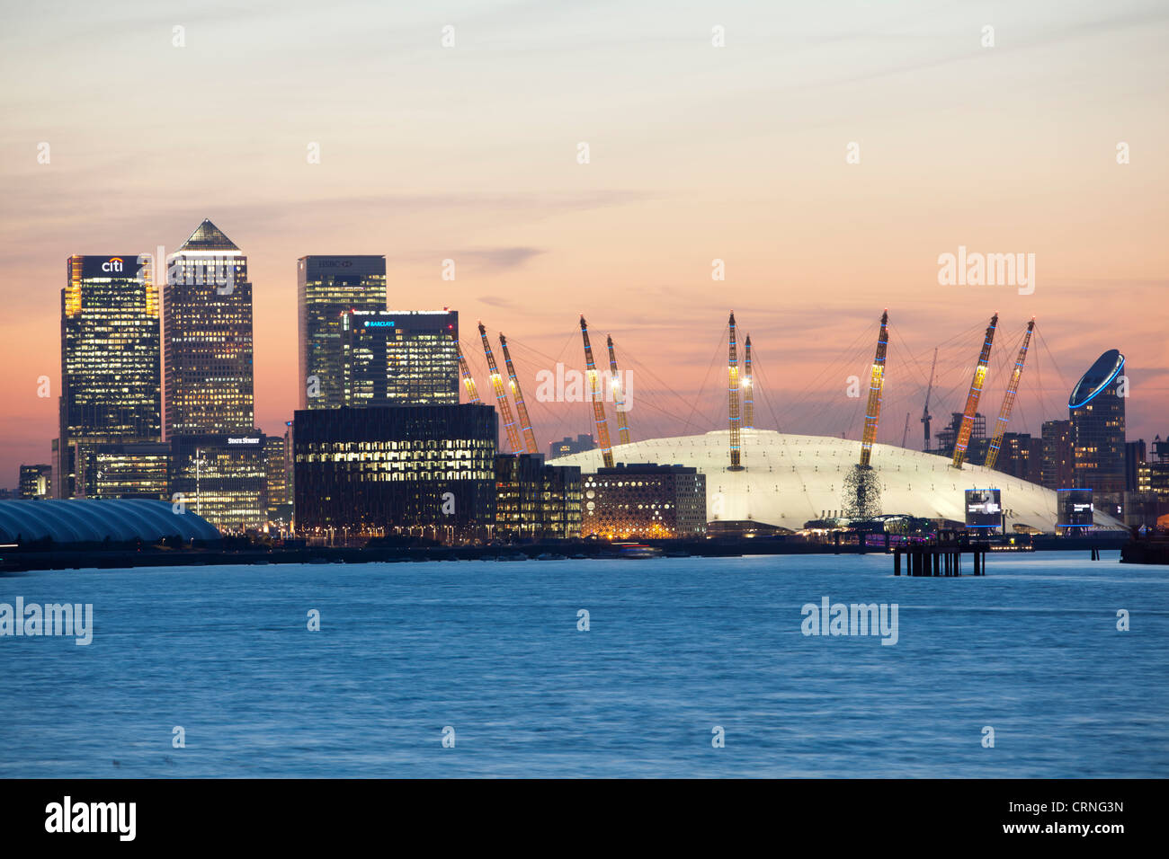 A view down the River Thames towards the O2 Arena and Canary Wharf at sunset. Stock Photo