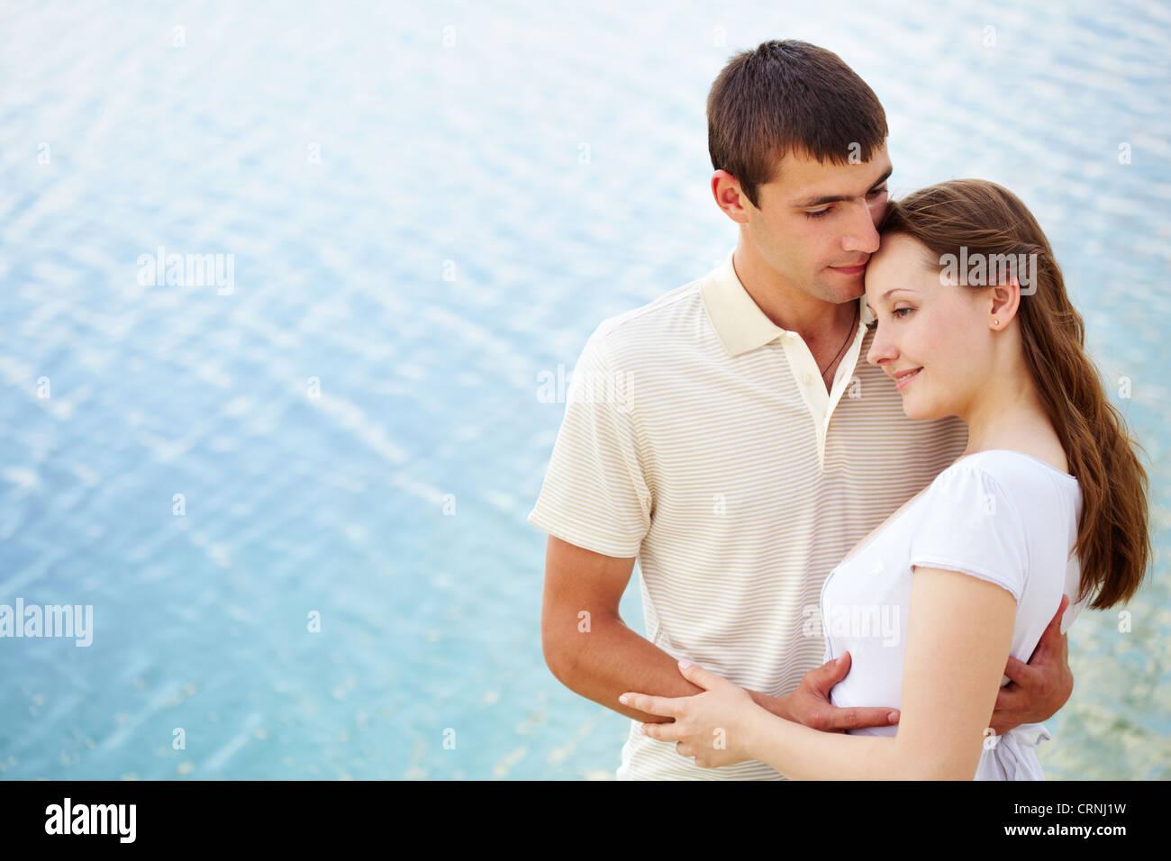 Guy embracing tenderly his girlfriend - Stock Image