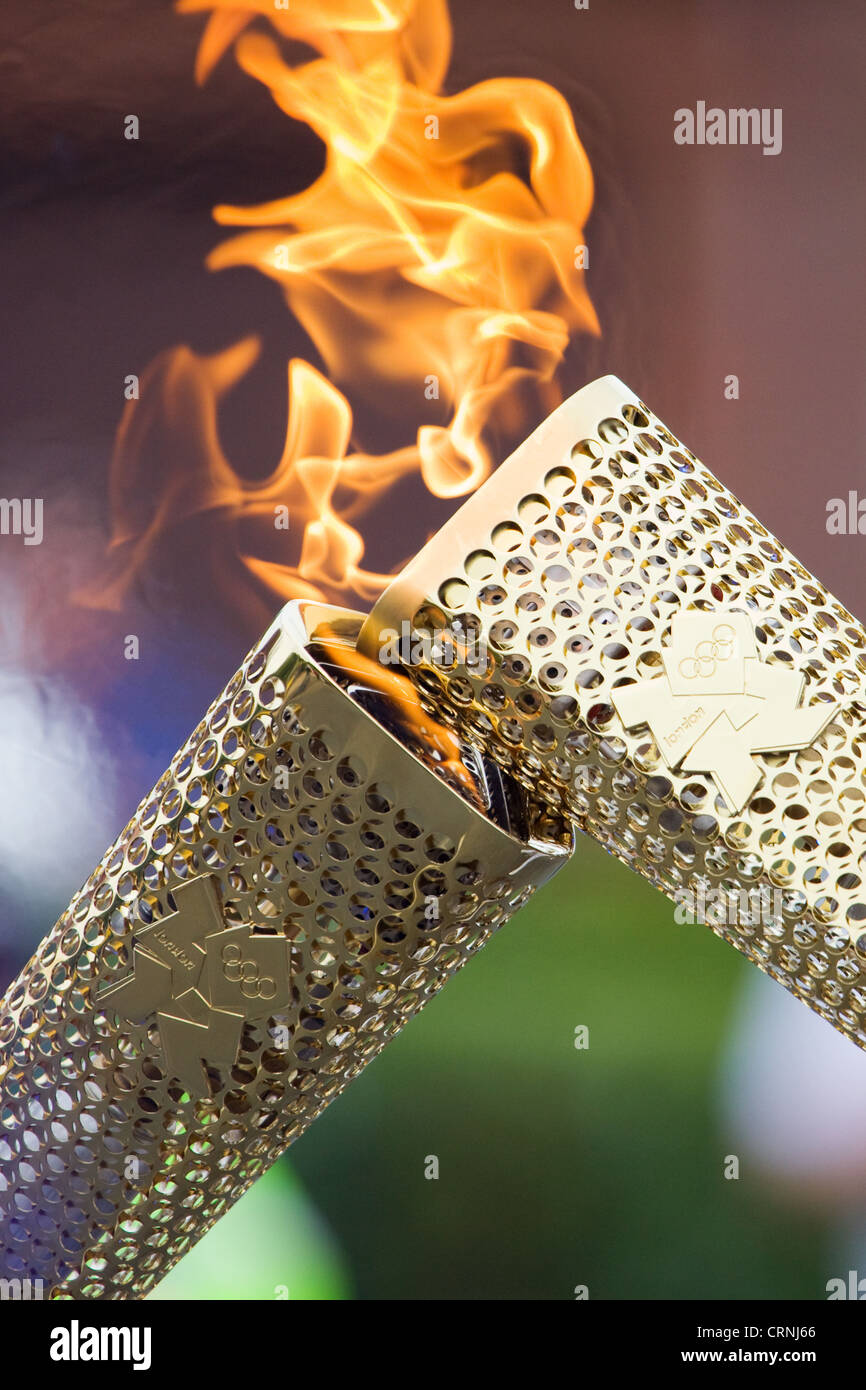The Olympic Flame is passed from one torch to the next, a process known as kissing, during the torch relay. - Stock Image