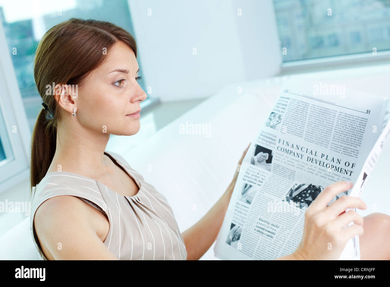 Attractive business lady with a newspaper being absorbed in her thoughts - Stock Image