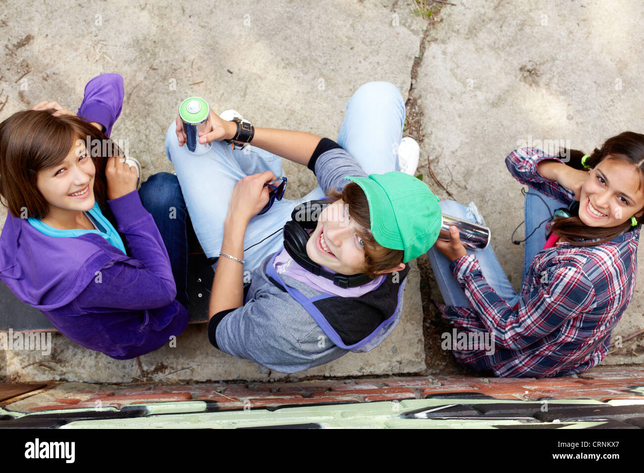 Group of teenagers with aerosol paint sitting and looking up at the camera - Stock Image