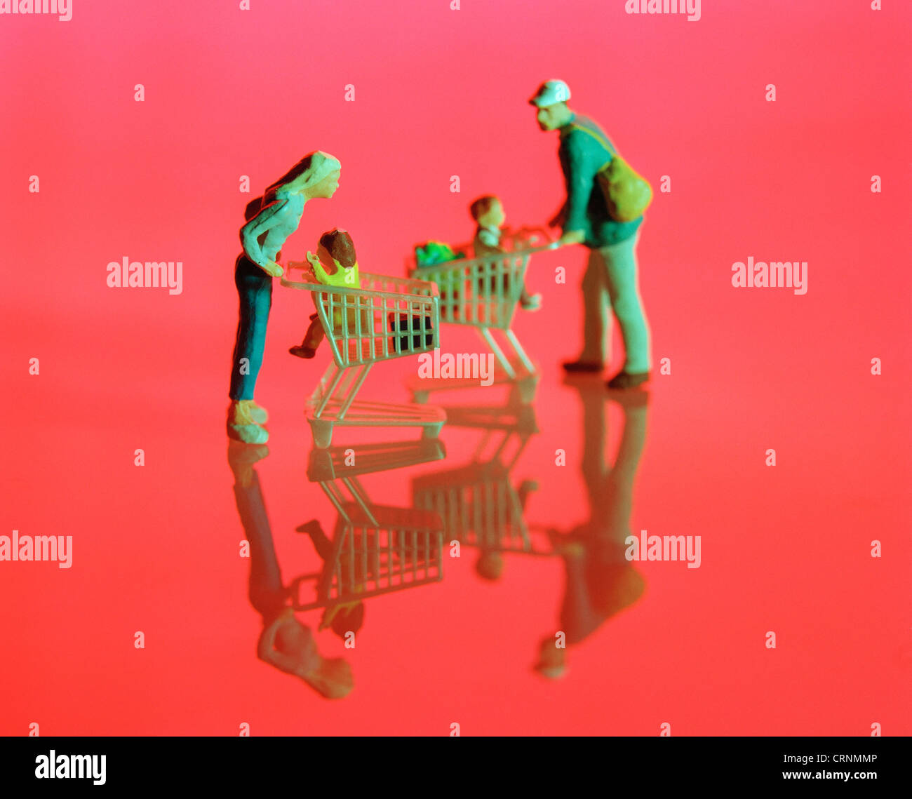 Miniature Figures with cart before red Flaeche - Stock Image