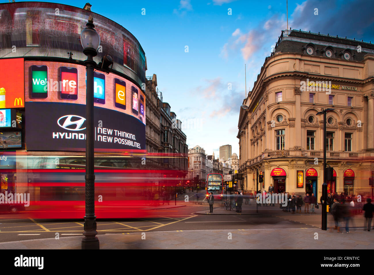 Red London double decker bus travelling through Piccadilly Circus in London's West End. - Stock Image