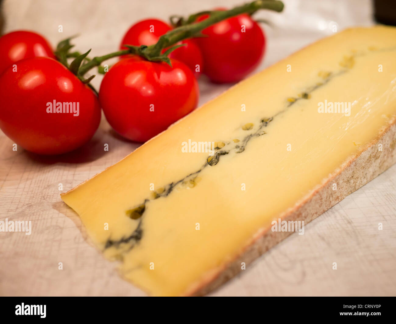 A slice of morbier cheese and a bunch of ripe tomatoes. Morbier is a semi-soft cows' milk cheese from France. - Stock Image