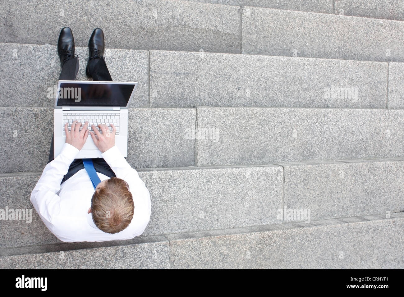 Business man sitting on stairs outdoor - Stock Image