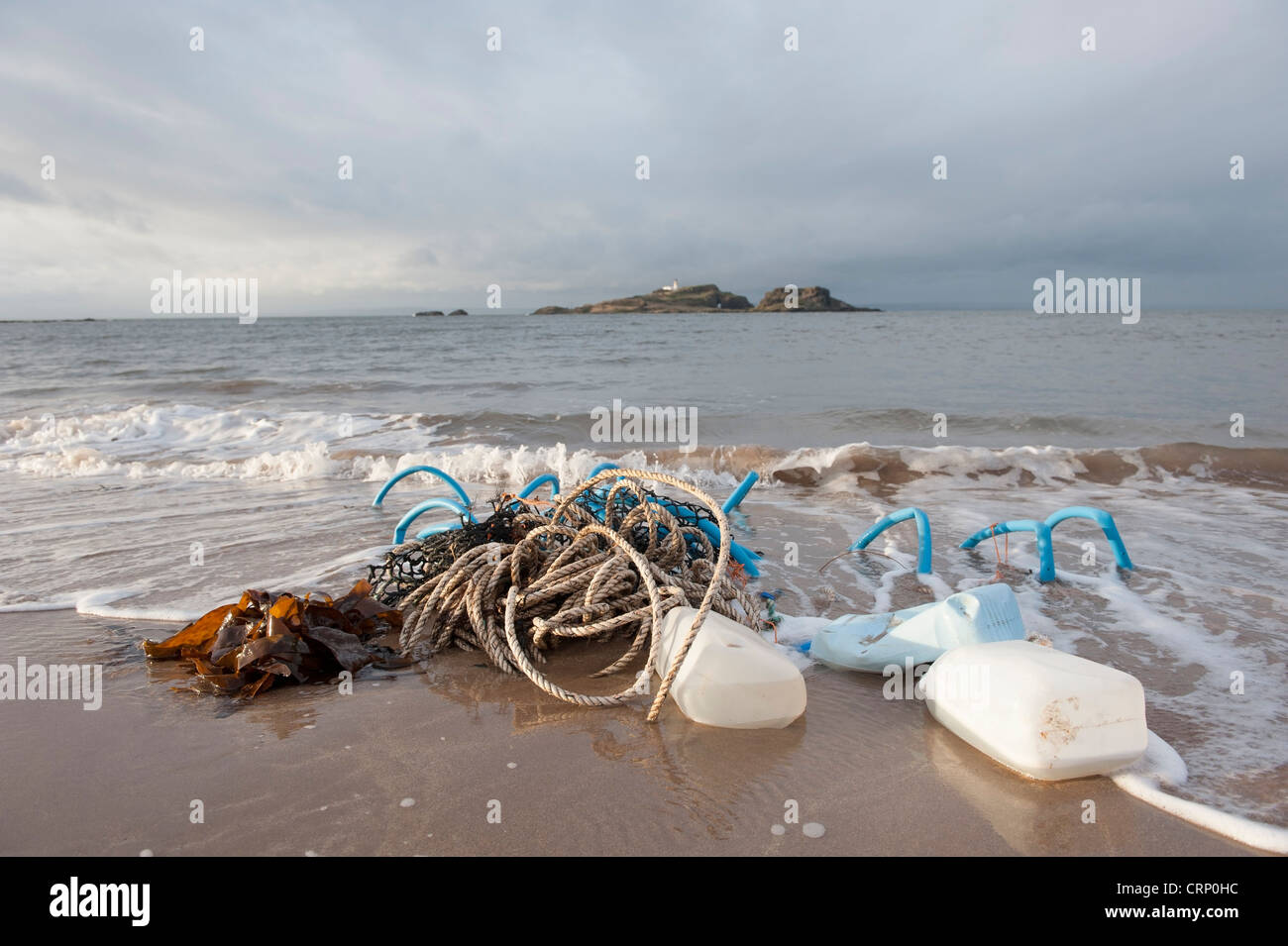 Broken lobster pots washed ashore on a beach after a storm, with the Island of Fidra on the horizon, Scotland. - Stock Image