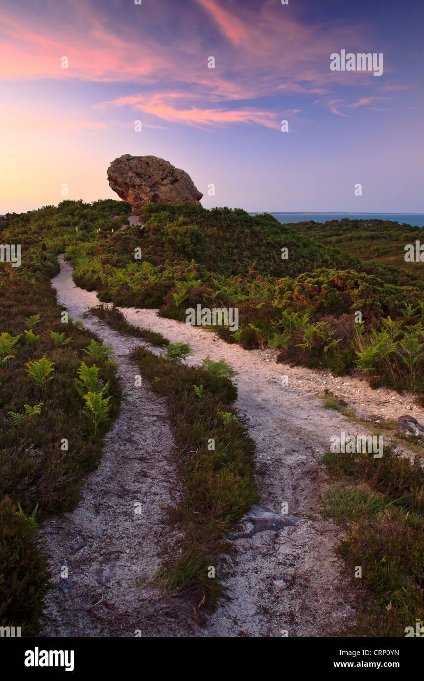 Sunset at Agglestone Rock, a large sandstone rock on Studland Heath. - Stock Image