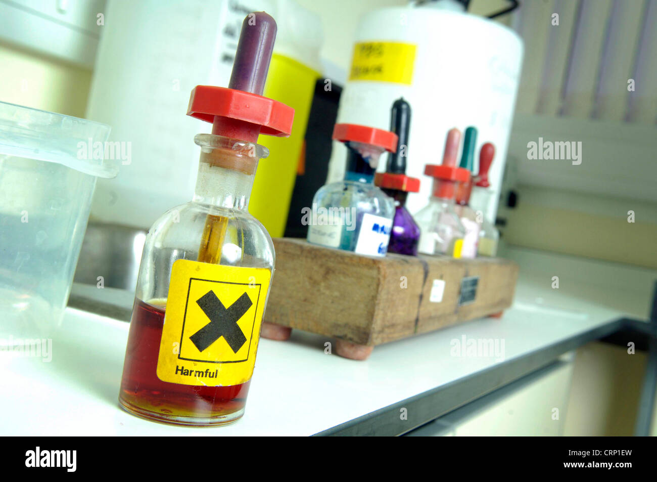 A pipette bottle containing yellow liquid marked 'Harmful' is placed in front a rack of bottles on a laboratory - Stock Image