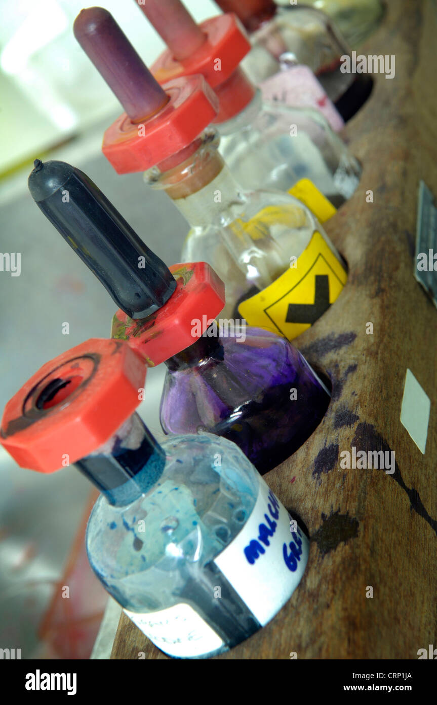 A rack of pipette bottles, some containing harmful liquids, on a laboratory workbench. - Stock Image