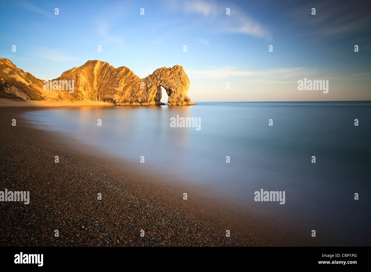 The sun casts warm light onto Durdle Door, a natural Limestone arch near Lulworth Cove, part of the UNESCO Jurassic - Stock Image