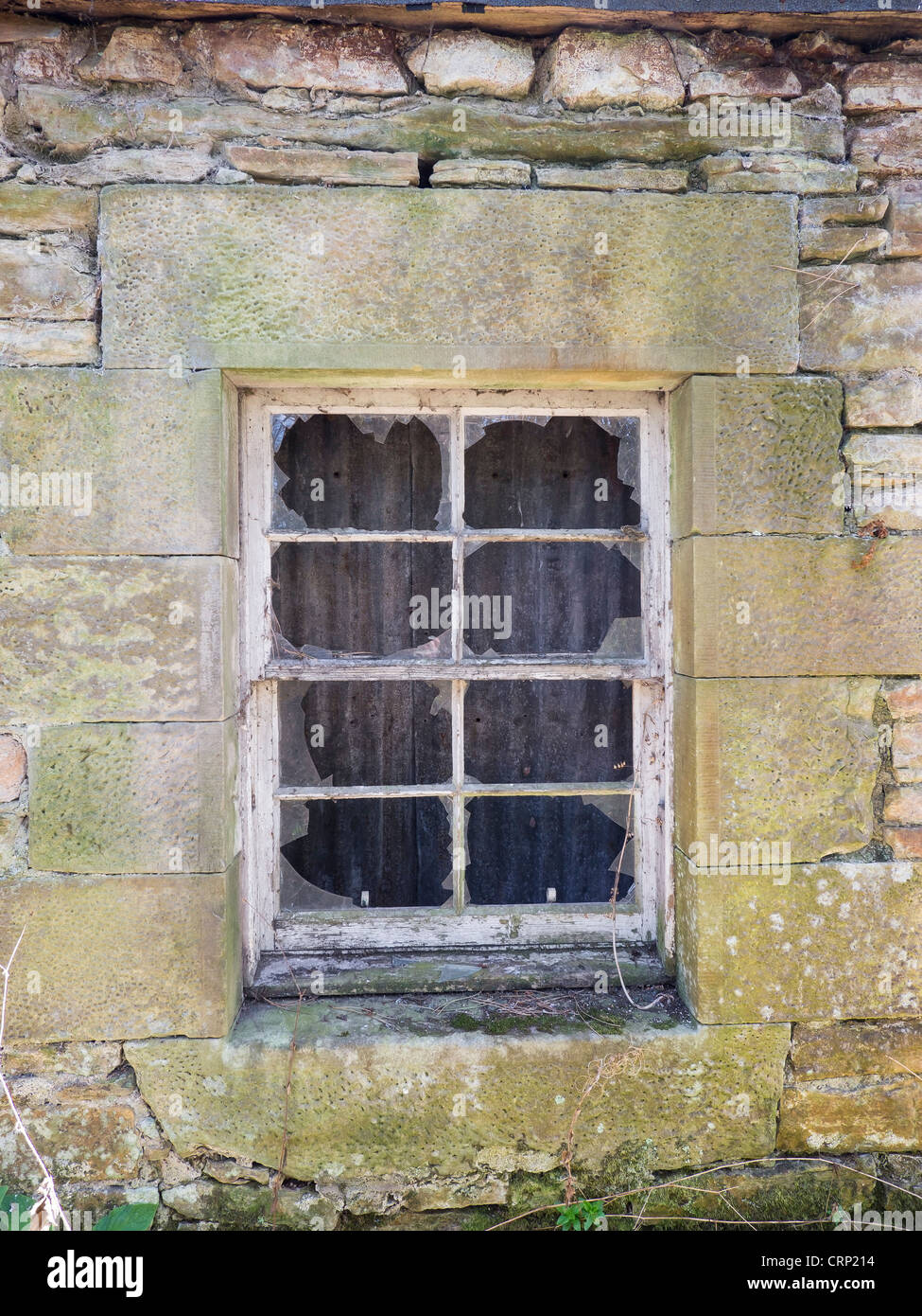 A broken window in an old derelict stone cottage in Scotland. - Stock Image
