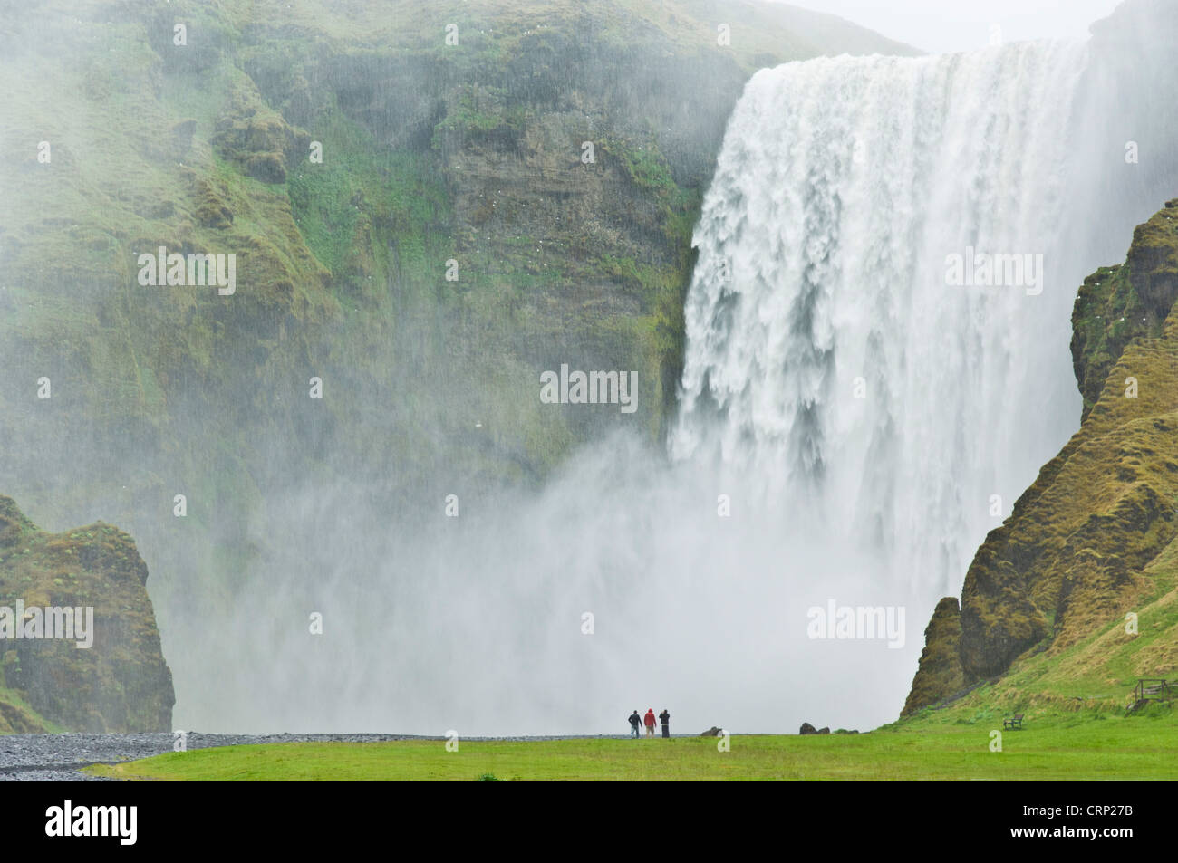 tourists stood in front of the powerful torrent of Skogafoss waterfall Skogar South Iceland EU Europe - Stock Image